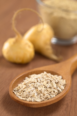 maca root: Oatmeal mixed with powdered maca or Peruvian ginseng (lat. Lepidium meyenii) on wooden spoon with fresh maca roots and maca powder (flour) in the back (Selective Focus, Focus in the middle of the oatmeal)