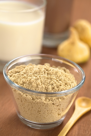 Powdered Maca or Peruvian ginseng (lat. Lepidium meyenii) in glass bowl with milk, chocolate drink and maca roots in the back (Selective Focus, Focus one third into the maca powder)