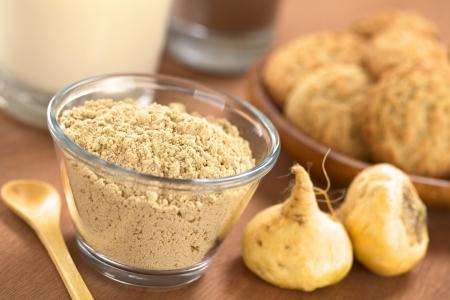 Poedervormige Maca of Peruviaanse ginseng (lat. Lepidium meyenii) in glazen kom met melk, chocolade drank, maca cookies en maca wortels (Selectieve Aandacht, focus Een derde in de maca poeder)
