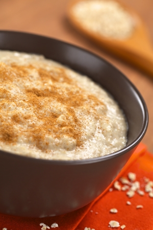 maca: Taz�n de fuente de gachas de avena cocida mezclada con polvo de maca o ginseng peruano (lat. Lepidium meyenii) con canela en la parte superior (enfoque selectivo, foco en el centro de la papilla de avena) Foto de archivo