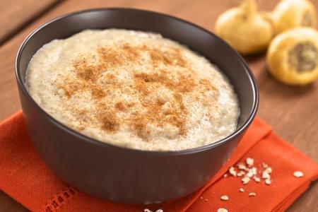 Bol de gruau cuit mélangé avec de la poudre de maca ou ginseng péruvien (lat. Lepidium meyenii) avec de la cannelle sur les racines de maca haut et à l'arrière (point sélective, Focus dans le milieu de la bouillie)