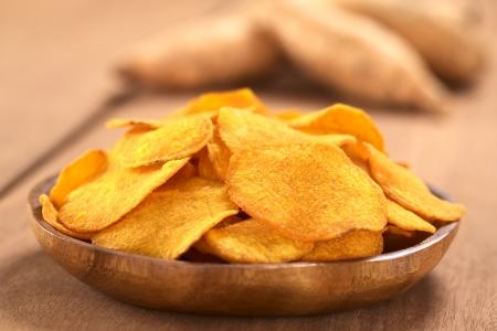 Krokante Peruaanse zoete aardappel chips op houten plaat met zoete aardappelen in de rug (selectieve aandacht, Focus op het midden van de zoete aardappel chip in de voorkant) Stockfoto