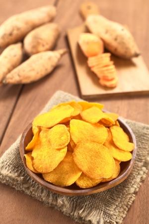 camote: Crujientes papas fritas de camote peruano en la placa de madera con patatas dulces en la parte posterior (Enfoque, Enfoque tercera en los chips de batata)