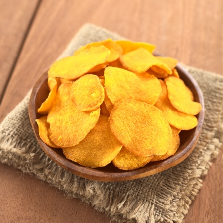 Crispy Peruvian sweet potato chips on wooden plate (Selective Focus, Focus on the lower part of the sweet potato chips) photo
