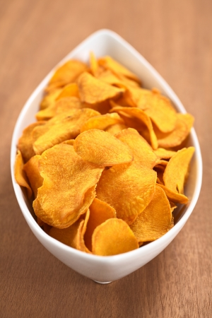 potato chip: Crispy Peruvian sweet potato chips in white ceramic  bowl on wood (Selective Focus, Focus one third into the sweet potato chips) Stock Photo