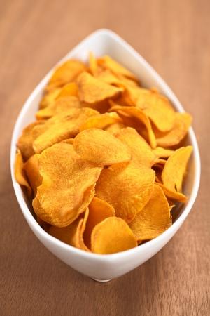camote: Crujientes papas fritas de camote peruano en un tazón de cerámica blanca en la madera (enfoque selectivo, foco en un tercio de los chips de batata) Foto de archivo