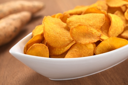 potato chips: Crispy Peruvian sweet potato chips in white ceramic bowl with sweet potatoes in the back (Selective Focus, Focus one third into the sweet potato chips)