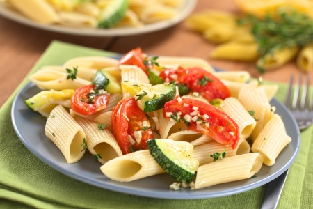 Vegetarian penne pasta dish with baked zucchini and tomato spiced with thyme and garlic (Selective Focus, Focus one third into the dish) photo
