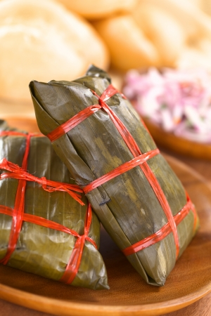 Peruvian tamales wrapped in banana leaves, in which they are cooked. Inside is a a corn-based dough with meat. Tamales in Peru are traditionally consumed as breakfast on Sundays accompanied by buns, limes and salsa criolla (onion salad) (Selective Focus,  Stockfoto