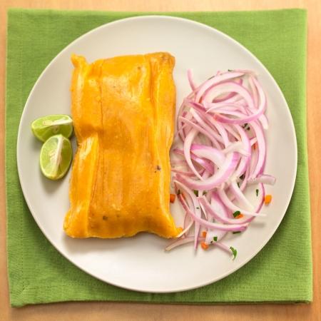 Tamale péruvienne (traditionnellement consommé au petit déjeuner le dimanche) à base de maïs et de poulet servi avec salsa criolla (salade d'oignons) et limes (sélective Focus, Focus sur le haut de la tamale)