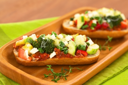 Baked vegetarian open sandwich (red bell pepper, broccoli, zucchini, scallion and cheese on spicy tomato sauce on a bun) on wooden plate (Selective Focus, Focus on the front of the broccoli)  Stock Photo