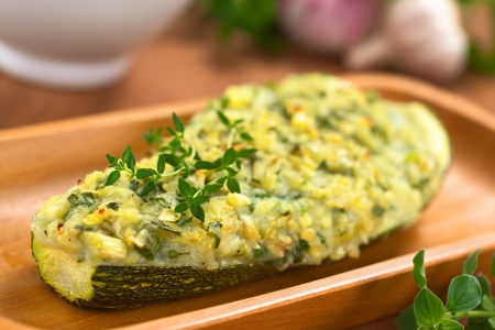 prepared potato: Baked zucchini stuffed with mashed potato, cheese and herbs (thyme, oregano, parsley, garlic) garnished with thyme served on wooden plate (Selective Focus, Focus on the front of the thyme garnish on the zucchini)