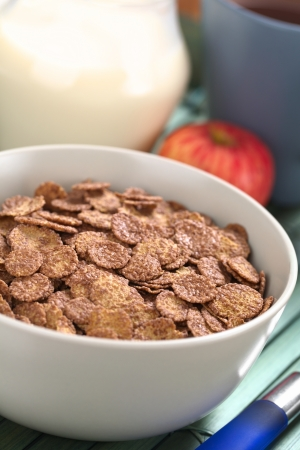 Bowl of chocolate corn flakes cereal with apple, cup of coffeetea and a jug of milk in the back (Selective Focus, Focus in the middle of the cereal) photo