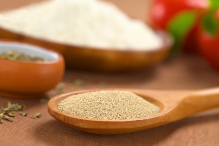 leavening: Basic ingredients of a pizza: Active dry yeast on wooden spoon with oregano, flour, tomato and basil in the back (Selective Focus, Focus one third into the dry yeast)   Stock Photo