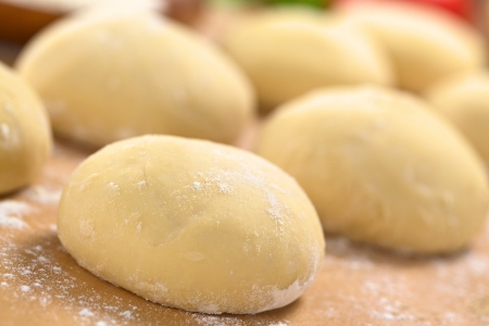 Small balls of fresh homemade pizza dough on floured wooden board (Selective Focus, Focus one third into the first pizza dough)