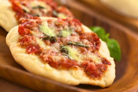 Crispy homemade Pizza Margherita or Pizza Mozzarella (pizza with tomato, basil and cheese) on wooden plate (Selective Focus, Focus one third into the first pizza) Stock Photo - 15323600