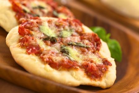 Crispy zelfgemaakte pizza Margherita of Pizza Mozzarella (pizza met tomaat, basilicum en kaas) op houten plaat (Selectieve Aandacht, focus Een derde in de eerste pizza) Stockfoto