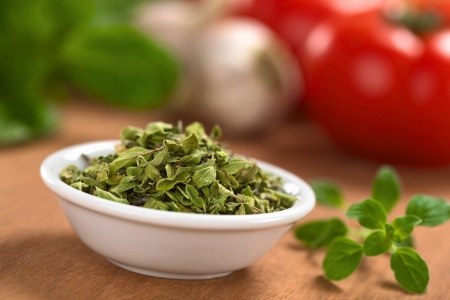dried leaf: Dried oregano leaves in small bowl with fresh oregano on the side, tomato, garlic and basil in the back (Selective Focus, Focus one third into the dried oregano leaves)