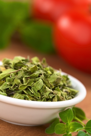 Dried oregano leaves in small bowl with fresh oregano on the side, tomato and basil in the back (Selective Focus, Focus one third into the dried oregano leaves) photo