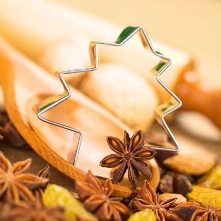 Christmas Baking. Tree shaped cookie cutter with star anise on wooden spoon surrounded by raisins and nuts, with a rolling pin in the back (Selective Focus, Focus on the left side of the cookie cutter and on the anise on the spoon) Stock Photo - 15366524