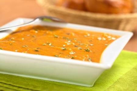Kom van verse huisgemaakte zoete aardappel soep met tijm (selectieve aandacht, focus Een derde in de soep)