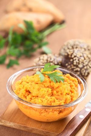 pure de papas: La batata se extendió en un recipiente de cristal adornado con perejil con pequeños bollos integrales sésamo sobre tabla de madera