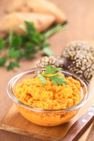 mashed potatoes: Sweet potato spread in glass bowl garnished with parsley with small sesame-wholegrain buns on wooden board Stock Photo