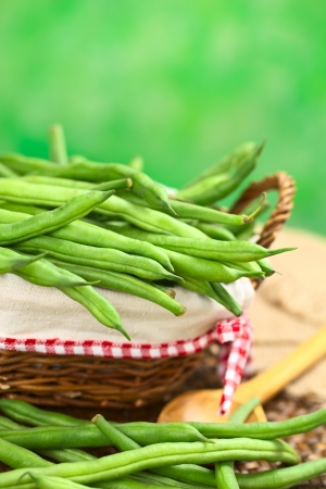french bean: Fresh raw green beans in basket with green background (Selective Focus, Focus on the beans in the middle of the image) Stock Photo