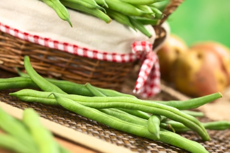 common bean: Fresh raw green beans in front of a basket with potatoes in the back (Selective Focus, Focus on the long bean one third into the image ) Stock Photo