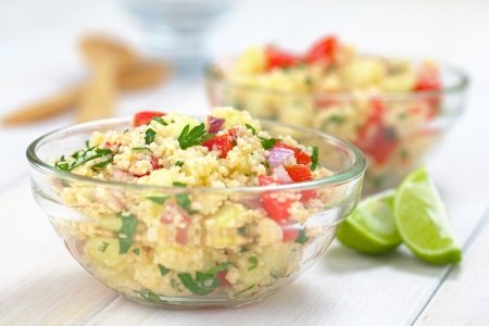 durum: Fresh homemade Tabbouleh, an Arabian vegetarian salad made of couscous, tomato, cucumber, onion, garlic, parsley and lemon juice served in a glass bowl  Selective Focus, Focus one third into the tabbouleh  Stock Photo