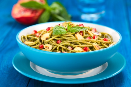Spaghetti with pesto, pomegranate and roasted almond halves garnished with a basil leaf and served in a blue bowl on blue wood, with glass of water, half pomegranate and basil leaf in the back  Selective Focus, Focus on the front of the basil leaf on the  photo
