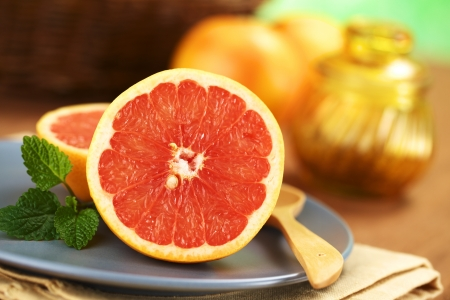grapefruit: Half of a pink-fleshed grapefruit on blue plate with mint leaf and wooden spoon