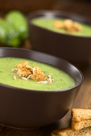 Zucchini cream soup with wholewheat croutons and roasted sunflower seeds served in brown bowl