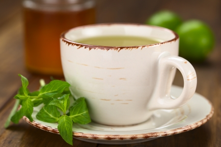 Freshly prepared mint tea out of fresh leaves served in a cup with leaves on the side Stock Photo - 22109925