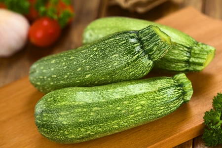 cucurbita: Raw zucchini on wooden board with other ingredients in the back Stock Photo