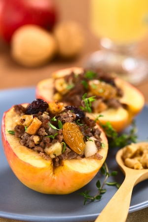 Savory baked apple filled with mincemeat, raisins, sultanas, onion and walnut, sprinkled with fresh thyme leaves on top (Selective Focus, Focus on the sultana in the front)    photo