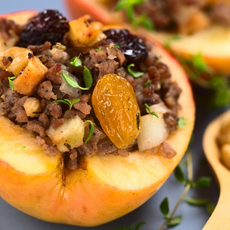 mincemeat: Savory baked apple filled with mincemeat, raisins, sultanas, onion and walnut, sprinkled with fresh thyme leaves on top (Selective Focus, Focus on the sultana)    Stock Photo