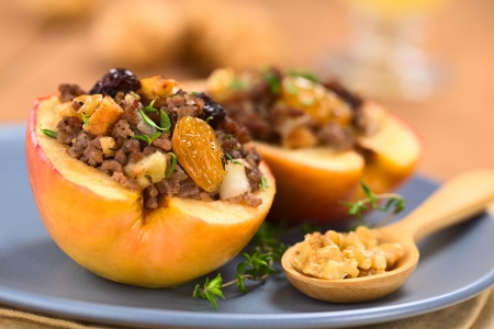 Savory baked apple filled with mincemeat, raisins, sultanas, onion and walnut, sprinkled with fresh thyme leaves on top served on blue plate with walnuts on wooden spoon  (Selective Focus, Focus on the sultana in the front)    photo