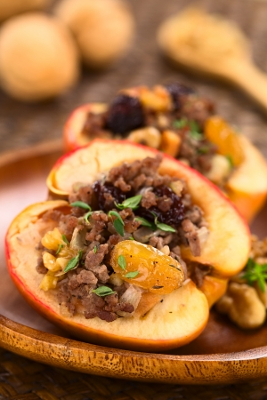 mincemeat: Savory baked apple filled with mincemeat, raisins, sultanas, onion and walnut, sprinkled with fresh thyme leaves on top with walnuts in the back (Selective Focus, Focus on the filling in the front)    Stock Photo