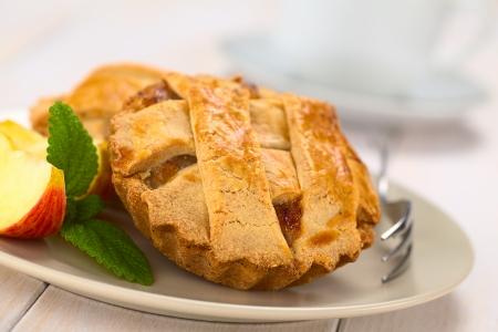 pie de manzana: Pastel de manzana redonda pequeña con la corteza de celosía con un tenedor pastel, hojas de menta y rodaja de manzana en un plato, taza en la parte posterior (enfoque selectivo, enfoque un tercio en el pastel) Foto de archivo
