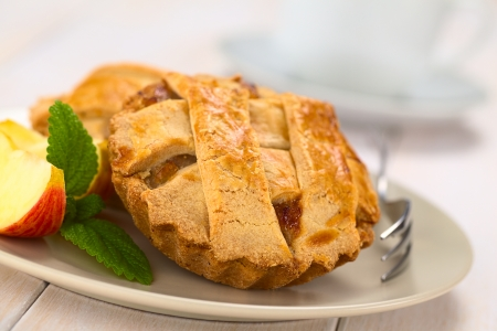 apple pie: Small round apple pie with lattice crust with pastry fork, mint leaf and apple slice on a plate, cup in the back  (Selective Focus, Focus one third into the pie)