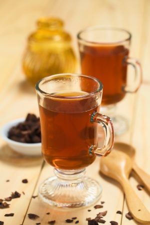 Fresh hot chocolate herbal tea made of cacao shell flakes, which is rich in flavonoids and antioxidants, served in glasses (Selective Focus, Focus on the front of the rim of the first glass) Stock Photo - 23177239
