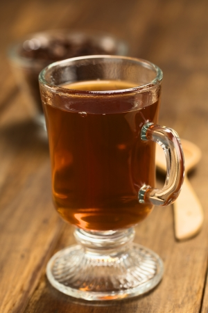 Fresh hot chocolate herbal tea made of cacao shell flakes, which is rich in flavonoids and antioxidants, served in glass on dark wood  (Selective Focus, Focus on the front of the rim of the glass) Stock Photo - 23177243