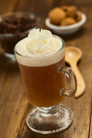 Fresh hot chocolate herbal tea made of cacao shell flakes, which is rich in flavonoids and antioxidants, served in glass with whipped cream on top on dark wood  (Selective Focus, Focus on the front of the cream) Stock Photo - 23177245
