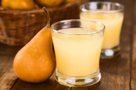 Pear juice in glass with Bosc pear on the side on dark wood (Selective Focus, Focus on the front rim of the glass)