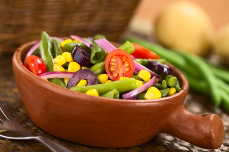 Fresh colorful vegetarian salad made of green beans, cherry tomatoes, sweet corn, black olives and red onions in rustic bowl (Selective Focus, Focus on the tomato in the middle)  photo