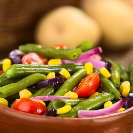 Fresh colorful vegetarian salad made of green beans, cherry tomatoes, sweet corn, black olives and red onions (Selective Focus, Focus one third into the salad)  photo