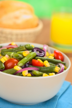 Fresh colorful vegetarian salad made of green beans, cherry tomatoes, sweet corn, black olives and red onions in bowl with orange juice and buns in basket in the back (Selective Focus, Focus one third into the salad)  photo