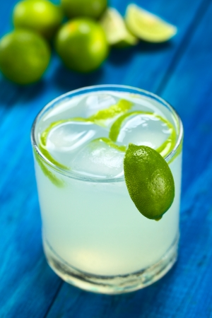 Freshly prepared refreshing lemonade out of limes with ice cubes and lime zest in glass garnished with a lime wedge on the rim; with limes in the back on blue wood (Selective Focus, Focus on the lime wedge on the rim) photo