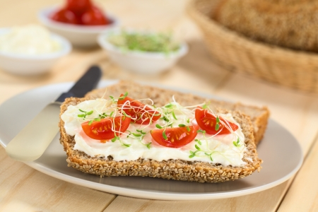 sandwich spread: Wholewheat bread spread with cream cheese, with cherry tomato and alfalfa sprouts on top served on plate (Selective Focus, Focus on the tomato in the front)